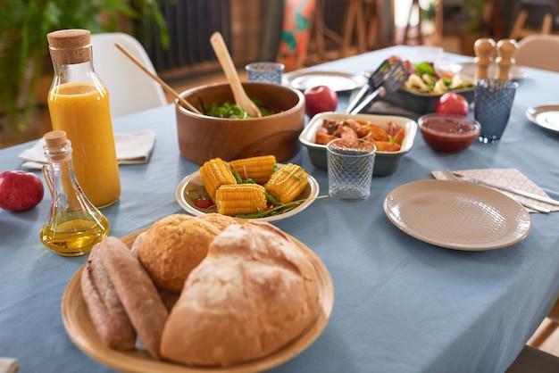 Крупный план обеденного стола с овощным салатом и мясом на нем, приготовленным для семейного ужина