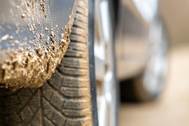 Закройте вверх пакостного колеса автомобиля при резиновая шина покрытая с желтой грязью.