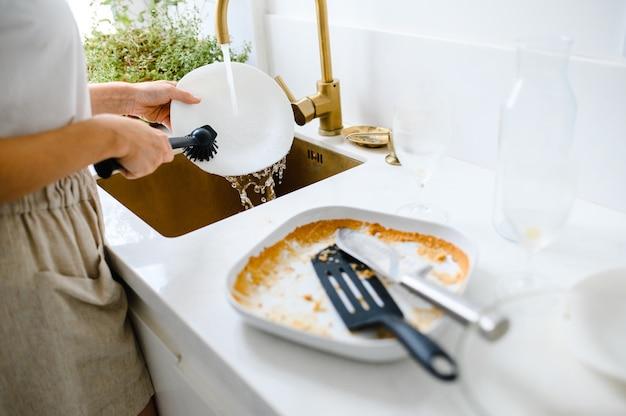 Закройте грязную посуду. женщина моет посуду на кухне