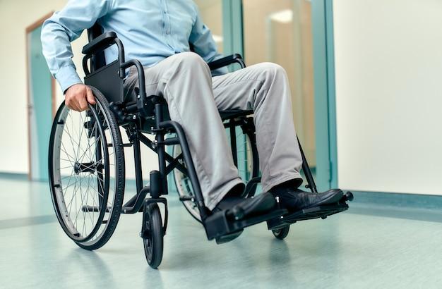 Крупный план пожилого человека-инвалида, сидящего в инвалидной коляске, за которым ухаживают в больнице, зрелого дедушки-инвалида в инвалидной коляске, концепции пожилых людей с инвалидностью.
