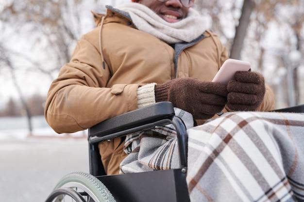 Крупный план инвалида в инвалидной коляске, использующего мобильный телефон на открытом воздухе