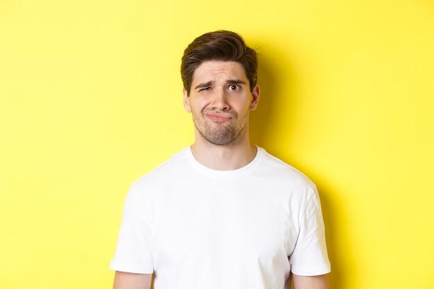 黄色の背景の上に立って、疑わしい、顔をゆがめた不満に見える白いtシャツを着た非難された若い男のクローズアップ。