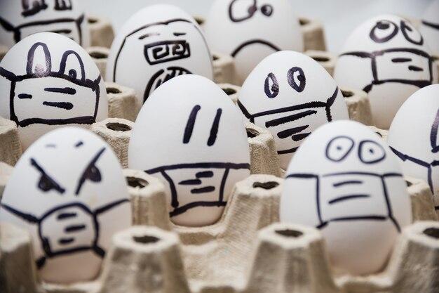 白の医療マスクを身に着けている落書き感情的な顔と多様な鶏のイースターエッグのクローズアップ
