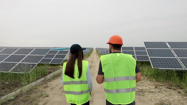 태양광 발전소를 걷는 특별한 제복을 입은 다양한 엔지니어들의 클로즈업. 태양 전지의 행입니다. 녹색 에너지 개념입니다. 태양광 패널 분야.