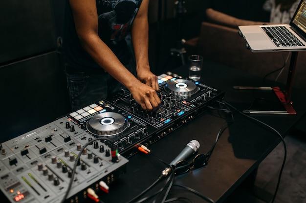 パーティーフェスティバルのターンテーブルで音楽を演奏するdjの手のクローズアップ