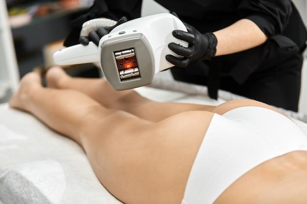 女性の体の上に美容装置を保持している医師の腕のクローズアップ