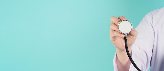 聴診器を持っている医者の手のクローズアップとミントグリーンまたはティファニーブルーの背景に長袖のガウンを着用してください