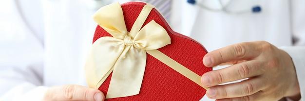 축제 황금 활과 심장 모양의 선물 상자를 들고 의사 손 클로즈업. 건강 한 심장의 상징으로 선물 상자와 심장. 의학 및 심장학 개념