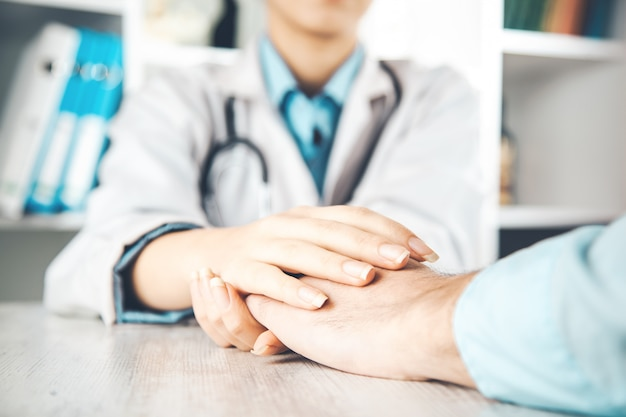 彼女の女性患者を安心させる医師の手のクローズアップ