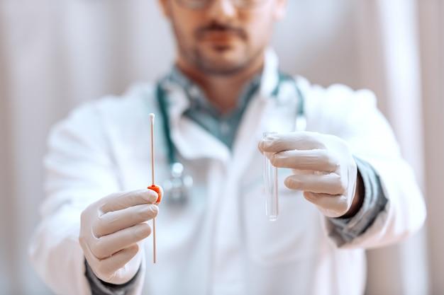 Закройте вверх доктора держа пробирку с образцом. резиновые перчатки на.