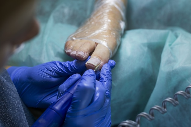Крупным планом врача в перчатках, делая процедуру для ног. педикюр в салоне красоты спа.