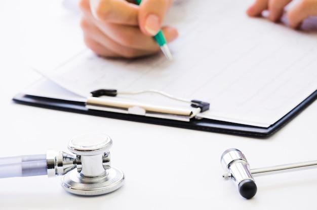 Конец-вверх ручки удерживания руки доктора проверяя медицинское заключение на доске сзажимом для бумаги