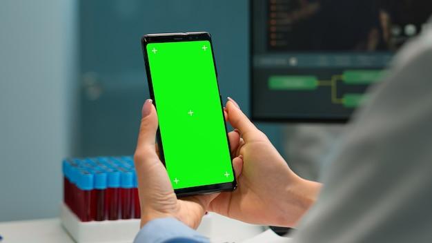 간호사가 혈액 샘플을 가져오는 동안 생물학 실험실 책상에 앉아 녹색 화면으로 전화를 들고 의사의 손을 닫습니다. 모형, 크로마 키 디스플레이가 있는 스마트폰을 사용하는 과학자