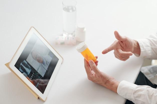 デジタルタブレットで同僚とオンライン会議をしながら、テーブルに座って薬の入ったボトルを指している医師のクローズアップ