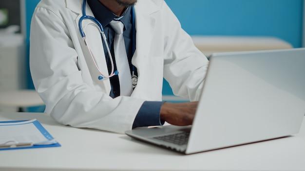 医療キャビネットのラップトップキーボードで入力する医師のクローズアップ