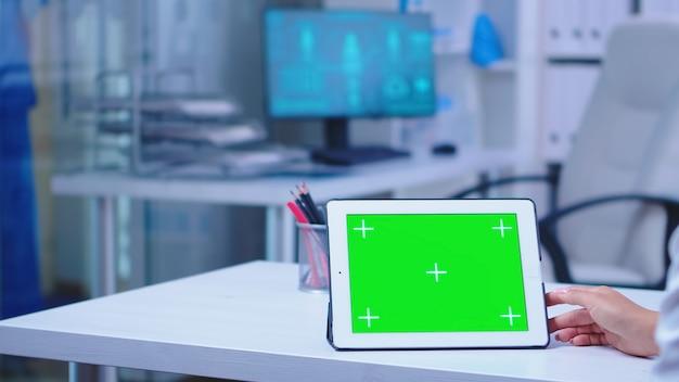 병원 캐비닛에 녹색 크로마 키가 있는 태블릿 컴퓨터를 사용하는 의사의 클로즈업. 의학 연구를 하는 교체 가능한 화면으로 태블릿 컴퓨터에서 작업하는 건강 클리닉의 의사.