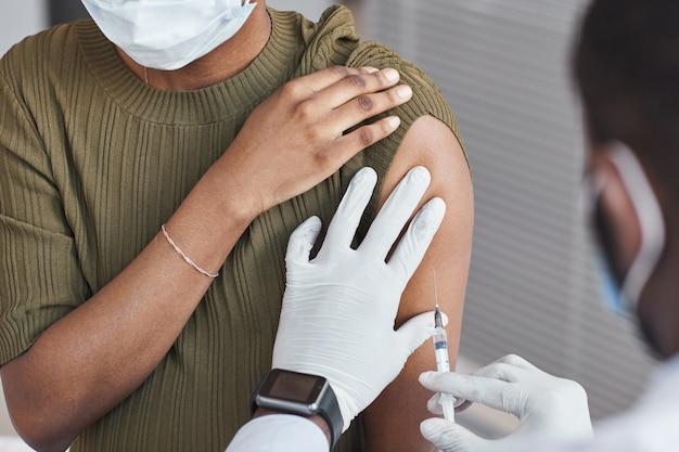 병원에서 여성에게 백신을 접종하는 의사의 클로즈업