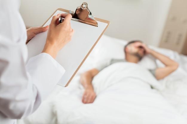 Крупным планом врача, пишущего на медицинской карте, с пациентом, лежащим на больничной койке
