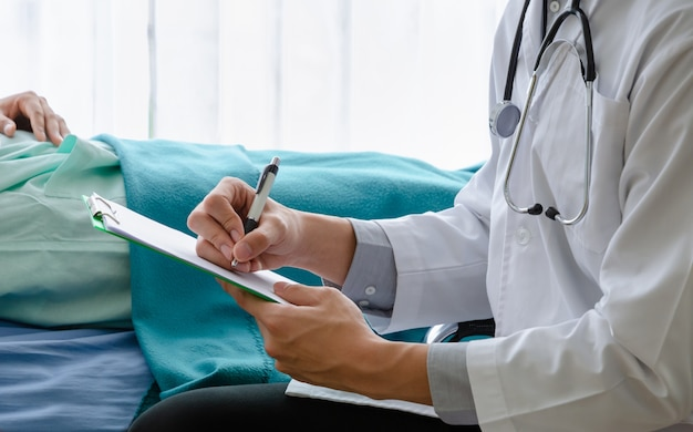 병원 침대에 누워있는 환자와 의료 차트에 작성하는 의사의 닫습니다.
