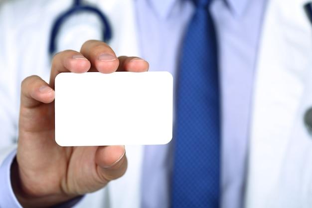 名刺を示す医師の手のクローズアップ