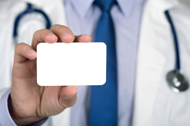 白い名刺を示す医師の手のクローズアップ。ヘルスケアと医療の概念