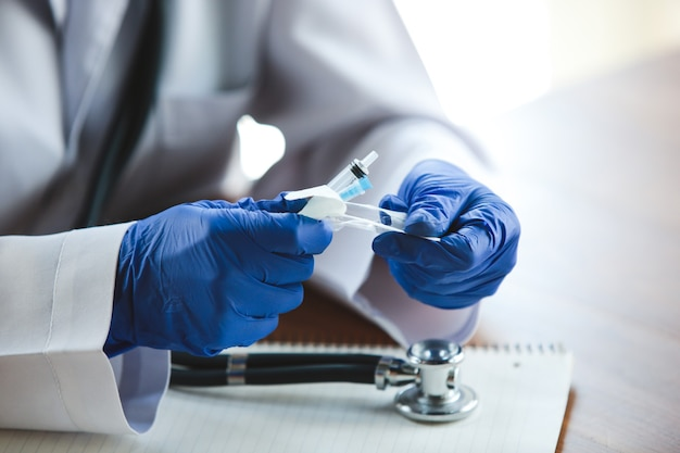 나무 테이블 배경에 청진기와 주사기가 있는 파란색 보호 장갑을 끼고 의사의 손을 닫아라