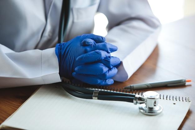 나무 탁자 배경에 청진기가 달린 파란색 보호 장갑을 끼고 있는 의사의 손 클로즈업