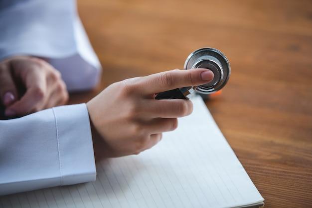 木製の背景に聴診器のシーツと錠剤で医師の手のクローズアップ