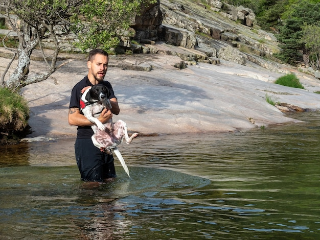 彼に湖で泳ぐことを教えるために子犬を保持している犬のトレーナーのクローズアップ。湖で泳ぐことを学ぶ黒と白の子犬。
