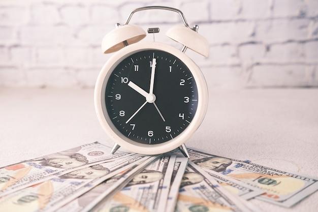 Крупным планом долларовые наличные и старый будильник на столе