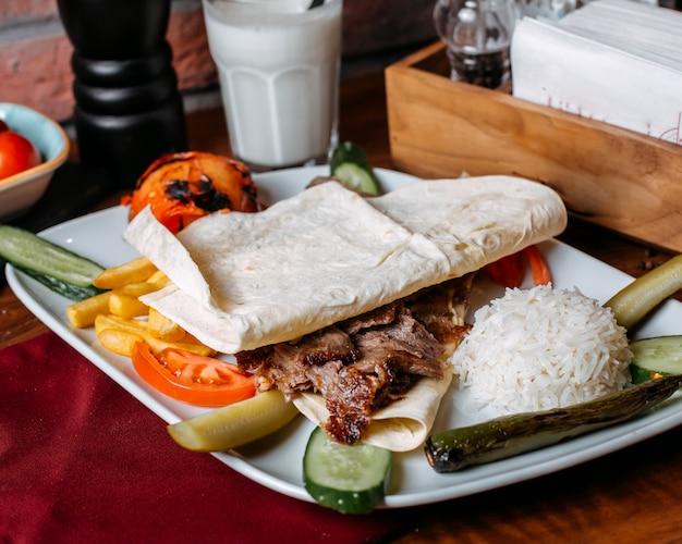 Крупным планом донер мясо с картофелем фри рисом и овощами на тарелке
