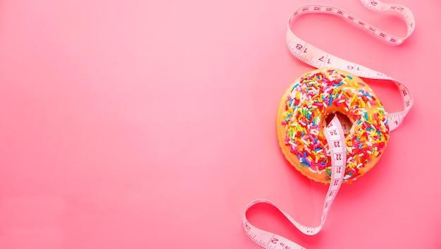 Закройте пончики и измерительную ленту на розовом фоне.