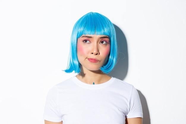 青いかつらで疑わしいしかめっ面のアジアの女の子のクローズアップ、左上隅に不信感を持って、立っています。