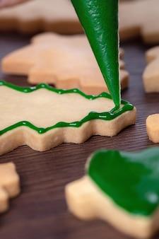 緑のアイシング、休日のお祝いの概念と木製のテーブルの背景にジンジャーブレッドのクリスマスツリーシュガークッキーを描くのクローズアップ。