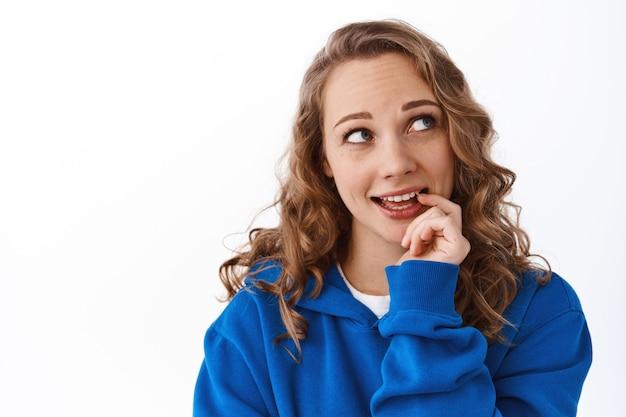 꿈결 같고 시시덕거리는 여성이 손가락을 물고, 오른쪽 상단 모서리를 사려 깊게 보고, 선택하고, 무언가를 결정하고, 흰 벽 위에 서 있습니다.