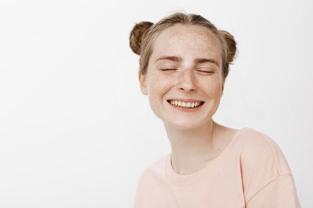 Крупный план мечтательной счастливой девочки-подростка, позирующей у белой стены