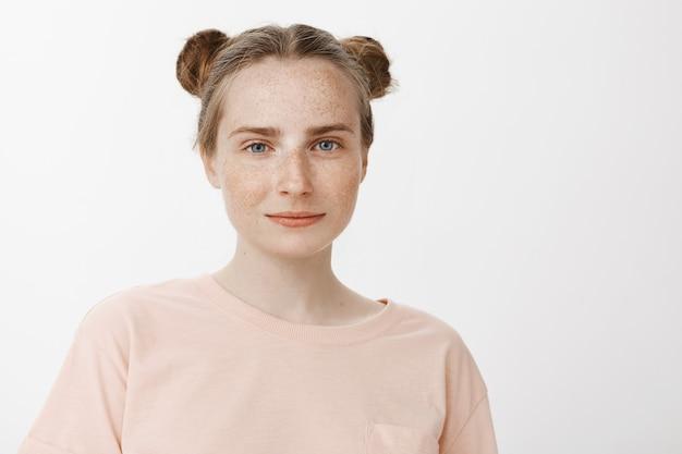 白い壁にポーズをとって夢のような笑顔の赤毛の10代の少女のクローズアップ