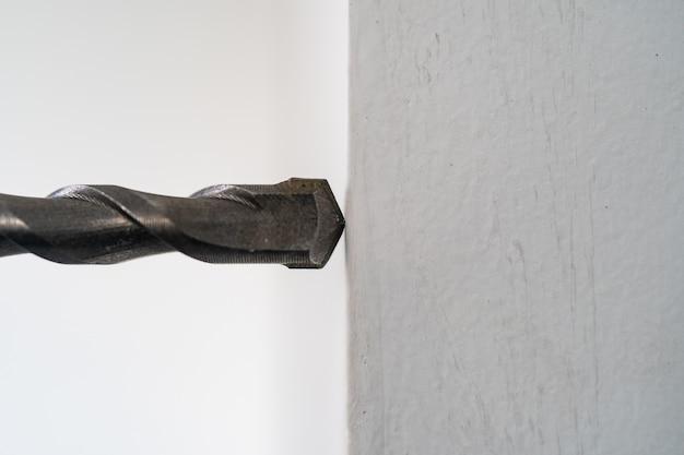 드릴링 기계의 클로즈업입니다. 작업자는 드릴링 머신을 사용하여 콘크리트 벽에 구멍을 뚫습니다.