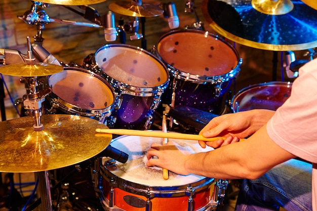 Заделывают барабанщика, играющего на ударной установке в студии