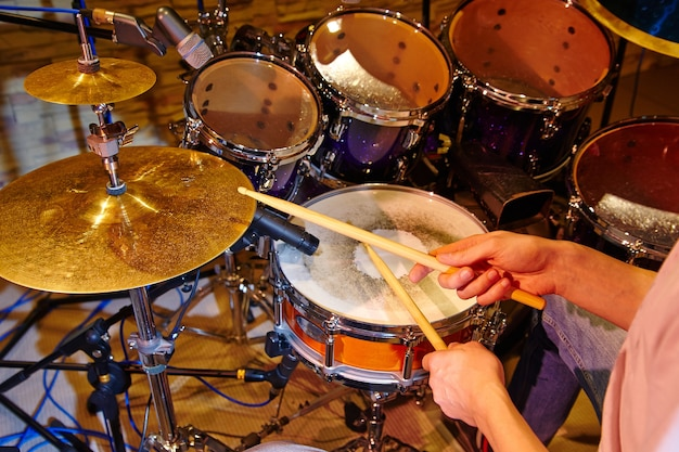 スタジオでドラムキットを演奏するドラマーのクローズアップ