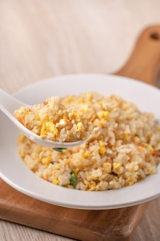 Крупным планом есть китайский жареный рис с креветками sergestid сакура в белой тарелке на яркой поверхности деревянного стола.