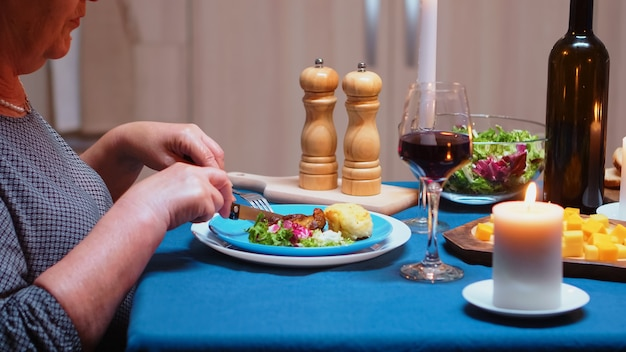 식탁에 앉아 저녁 식사, 부엌에서 건강한 음식을 먹는 것을 닫습니다. 식사를 즐기고 식당에서 기념일을 축하하는 노부부