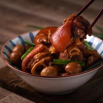 素朴なテーブルの上に箸でボウルに台湾料理の豚のナックルを食べるのクローズアップ
