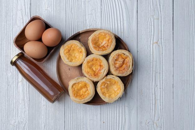 木の板に卵のタルトのクローズアップ
