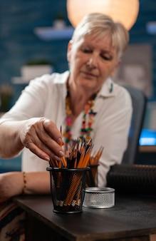 スタジオでテーブルの上に鉛筆を使用して年配のアーティストのクローズアップ