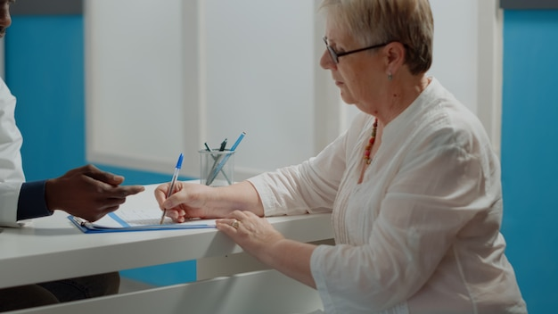 医療キャビネットの机に座っているペンで健康診断書に署名する高齢患者のクローズアップ。ヘルスケアの予約後に年配の女性からの紙のファイルに署名が必要な若い医師