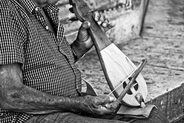 Крупным планом пожилой мужчина играет на каком-то традиционном инструменте
