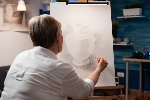 鉛筆でキャンバスに花瓶を描く年配の女性のクローズアップ