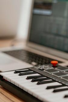 電動キーボードと焦点がぼけたラップトップのクローズアップ