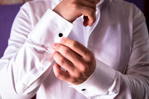 優雅な男性の手のクローズアップ。男は白いシャツを着た。